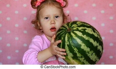 Very funny little girl trying to raise a large watermelon. Comic scene, humor