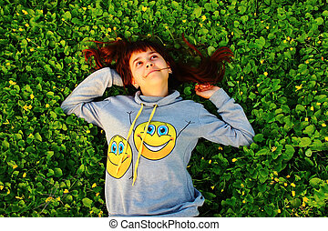 happy girl lying on the grass