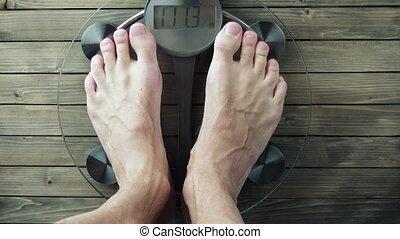 Very Heavy Man Stepping on the Bathroom Scale. 3840X2160 UHD...