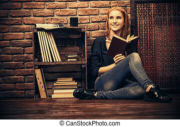 Cute young woman reads book at home. Loft style interior.
