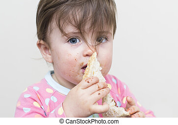 Very messy girl eating a sandwich