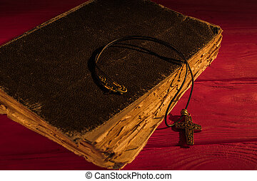 Very old ancient holy bible and neckalce cross.