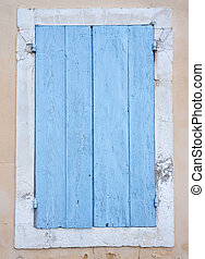 very old blue painted shutters on window in medieval french house