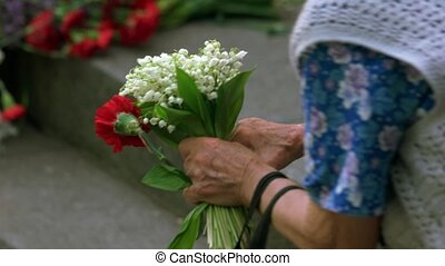 Very old lady with flowers at memorial day. Close up. Hands...