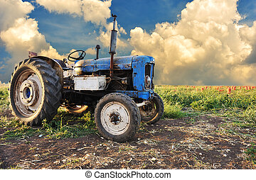 Very old tractor in field, different parts - no trademark at...