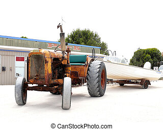 Very old tractor with new white motorboat on trailor. -...
