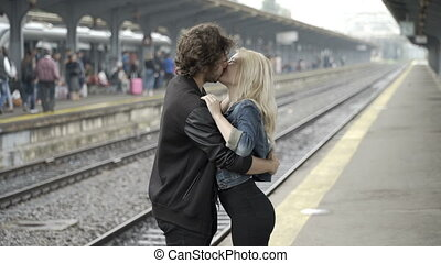Very passionate teen couple blowing kisses and hugging waiting in railway train station before trip