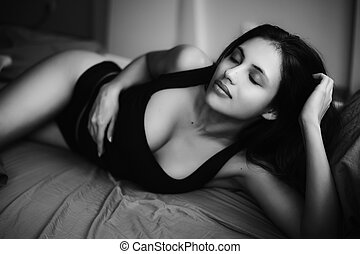 very sexy brunette woman lying on bed wearing black underwear. Erotic wake up, monochrome image