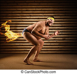 Very strange naked man farts by fire on the background of...