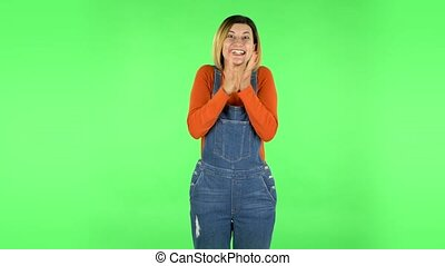 Very surprised girl with shocked wow face expression then shows thumb like sign. Brown-eyed girl with an earring in her ear dressed an orange sweater and denim overalls on a green screen in the studio