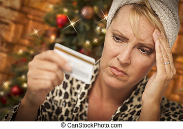 Upset Woman Holding Credit Card In Front of Christmas Tree