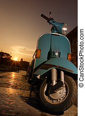 Vespa parked nearby the lake at the sunset
