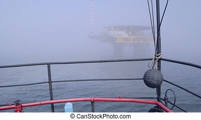 Vessel moving to offshore gas platform in the misty sea
