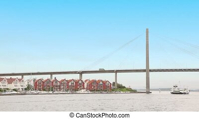 Vessels under huge pendant bridge near coastal village with...