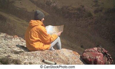 veste, touriste, gris, casquette, map., jeune, longs cheveux, jaune, sombre, girl, assied, montagnes, regarde