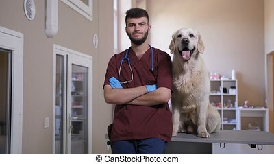 Vet in uniform with dog smiling arms crossed - Young...
