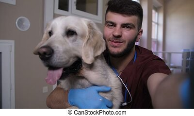 Vet making selfie on phone with dog at clinic - Young...