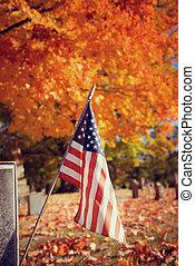Veteran flag in autumn cemetery