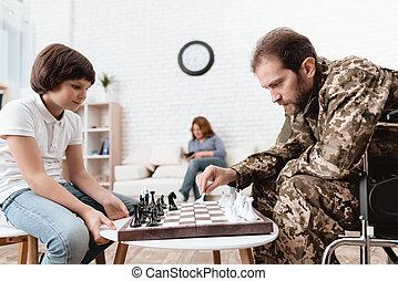veteran, in, militärische uniform, in, a, wheelchair., a, untauglicher mann, spiele, mit, seine, sohn, in, chess.