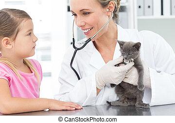 Veterinarian examining kitten with girl