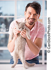 Veterinarian - Smiling man with a cute cat is looking at the...