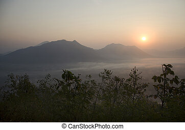 Vew of phu tok mountain with mist and sun at viewpoint in morning and sunrise time