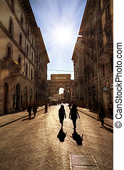 Florence street scene on the via degli speziali, backlit HDR with silhouettes in the street
