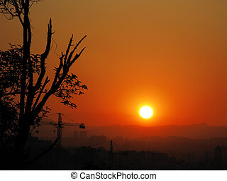 Vibrant and colorful orange sunset with silhouette of mountain