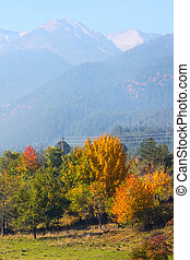 Vibrant autumn panorama background with colorful green, red, yellow trees and high mountains peaks