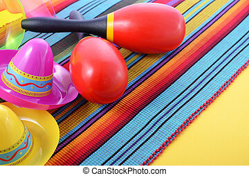 Vibrant Cinco de Mayo background with sombrero hats, maraccas, and tequila glasses on bright festive background, close up.