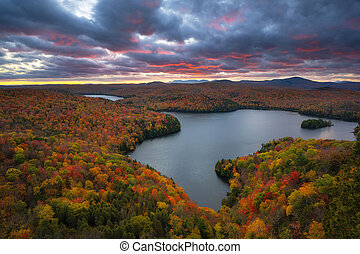Beautiful dusk colors over fall foliage surrounded Nichols Pond in Vermont