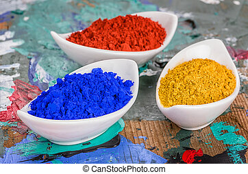 Vibrant color pigments in porcelain bowls on a wooden palette