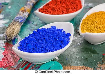Vibrant color pigments in porcelain bowls on a wooden...