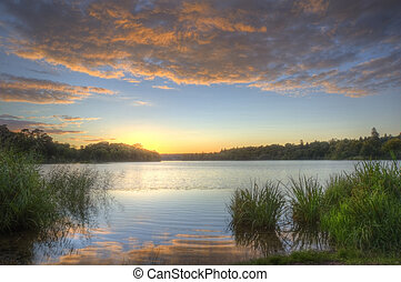 Vibrant colorful sunset over calm fishing lake with reflections