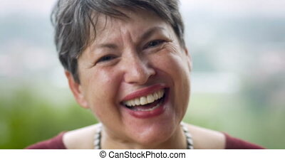 Vibrant mature senior woman in her 60s laughing at the...