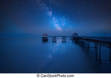 Vibrant Milky Way composite image over landscape of old pier stretching out to sea