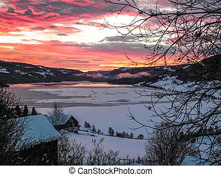 Vibrant sunrise over lake in winter landscape