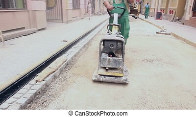 Vibrating machine is compacting soil at the construction site.