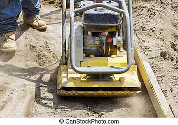 Vibratory plate compactor under construction worker uses ...