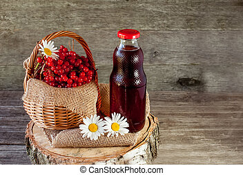 Viburnum berries in a basket on a napkin with daisies near the glass transparent bottle of juice. Rustic. Copy space.