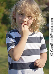 Vice - biting nails. - The blond boy in a striped shirt is...