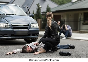 Bloody victim of car accident lying on the street