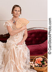 victorian woman with fan on couch