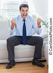 Victorious businessman cheering while sitting on sofa in...