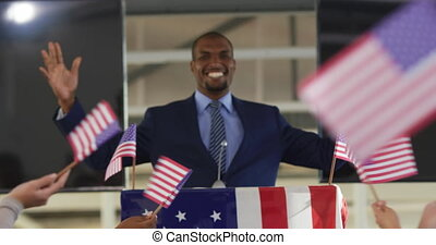 Front view of a smiling young African American man standing on a podium decorated with a US flag smiling and raising his arms in triumph at a political rally, with the arms of the audience seen from the back waving flags in the foreground