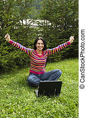 Victorious woman working on laptop in vacation - Victorious...