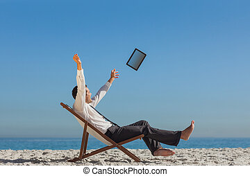Victorious young businessman relaxing on his deck chair throwing his tablet away