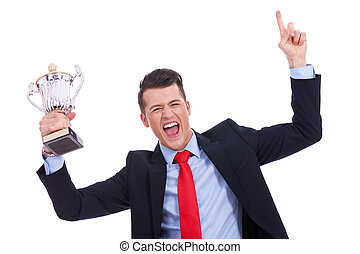 victory roar of a young businss man with a big trophy cup on...