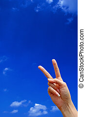 Victory sign with blue sky in the background