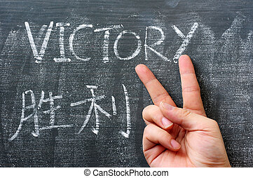 Victory - word written on a blackboard with a Chinese translation, with a hand gesture